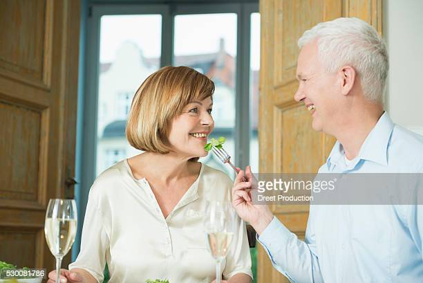Man feeding to woman, smiling
