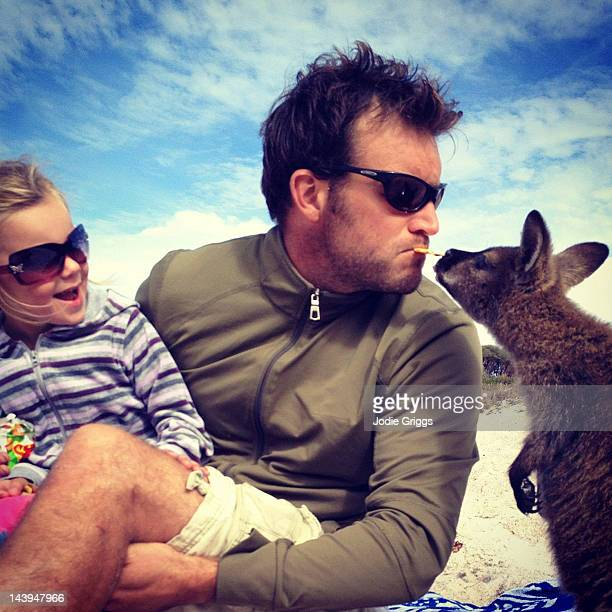 Man feeding wallaby by mouth with child watching