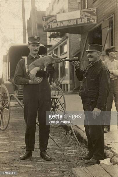 A man feeds a bottle of beer to a pig held by a second man as the pair stand in the street bear a truck and wagon builder's storefront Mansfield Ohio...