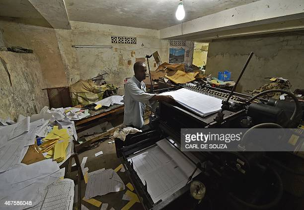 A man feeds an old original Heidelberg printing press with sheets of paper at the Daha printing press in Mogadishu on March 26 2015 The vintage...