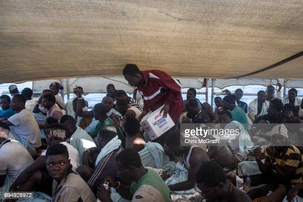 A man feeds refugees and migrants onboard the Migrant Offshore Aid Station Phoenix vessel enroute to Italy on June 11 2017 off Catania Italy An...