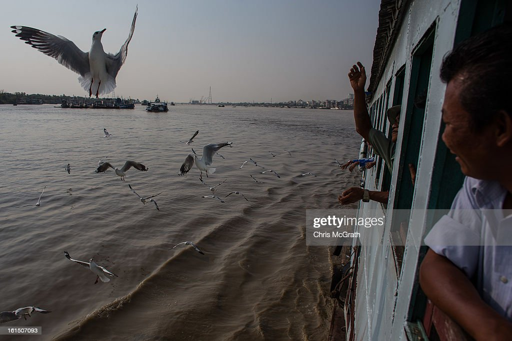 A man feeds seagulls from the window of a passenger ferry on February 11, 2013 in Yangon, Burma. Myanmar is going through rapid political and economic reforms initiated by the countries first civilian president Thein Sein after years of military junta rule.