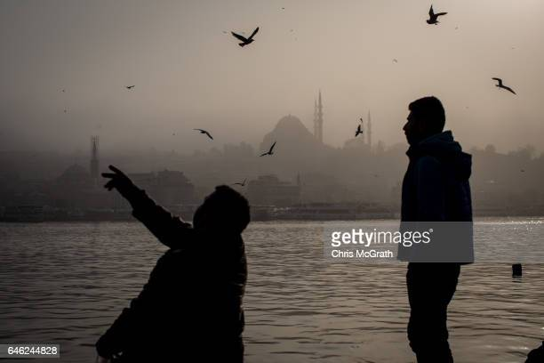 A man feeds seagulls in front of a fog covered Suleymaniye Mosque on February 28 2017 in Istanbul Turkey A fog descended across the Bosphorus Strait...