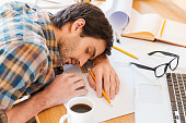 Top view of young man sleeping while sitting at his working place