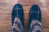 Man feet at home in pajamas and winter slippers