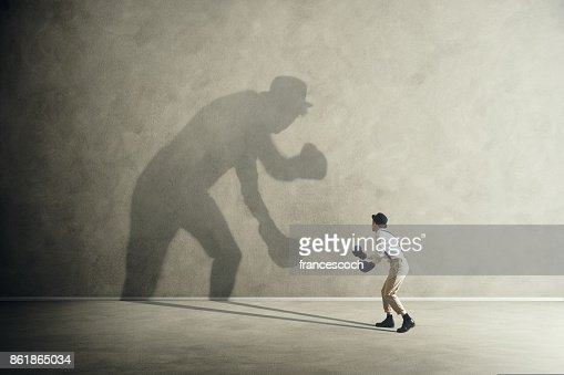 man fighting with his shadow, facing fears : Stock Photo