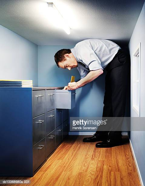 Man filing papers in office with low ceiling, side view