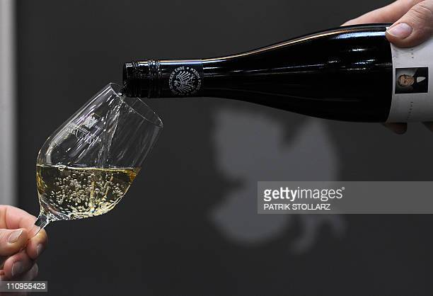 A man filles a glass with white wine out of a bottle with a logo of the German Rock band 'Die Toten Hosen' are on display at the 'Pro Wein' trade...