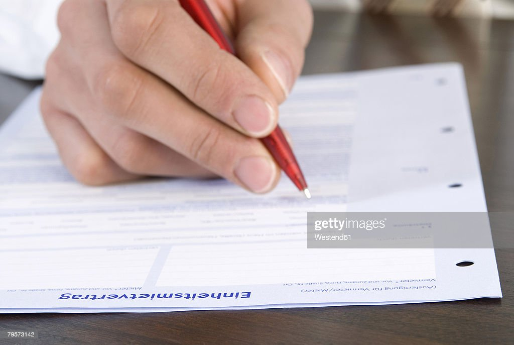 Man filling application form, close-up of hand