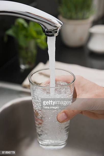 Man filling glass of water at sink