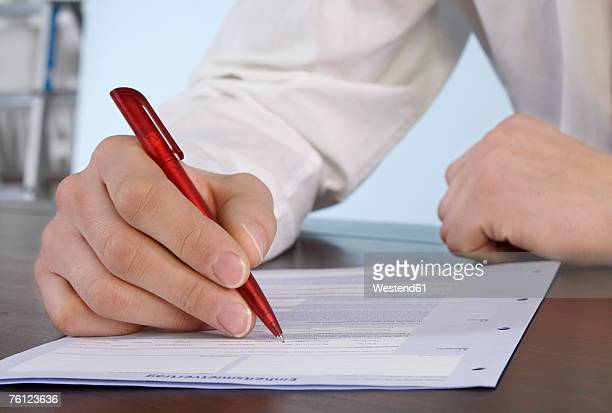 Man filling in application form, close-up