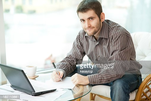 Man filling out a form looking at camera