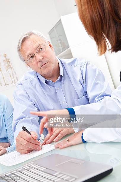 Man Filling Out Paperwork with Doctor or Physician