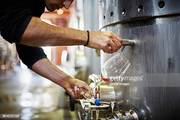 Man filling wine from storage tank in winery