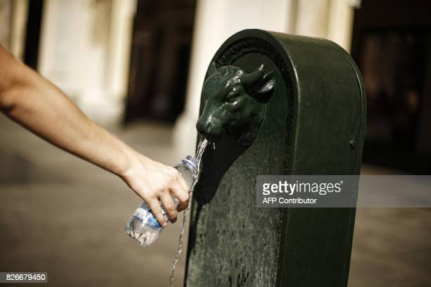 A man fills a bottle with water from a 'Turet' a typical fountain of Turin on August 5 2017 in Piazza San Carlo in Turin / AFP PHOTO / Marco...