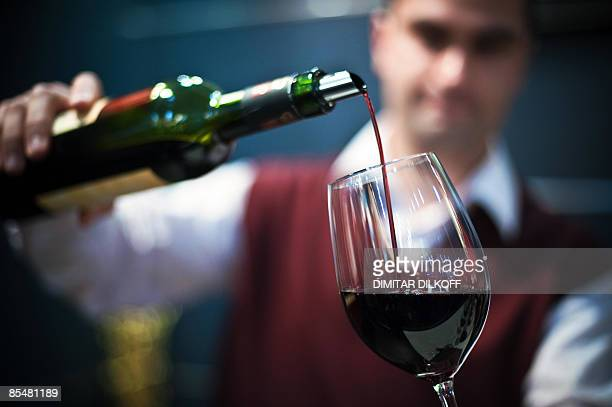 A man fills a glass with a red wine during the annual Winery 2009 international wine fair in the central Bulgarian city of Plovdiv on March 18 2009...