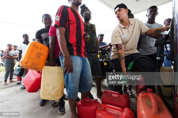 A man fills a jerrycan as people queue after a tank truck was able to resupply an outoffuel petrol station on March 26 in Cayenne French Guiana...