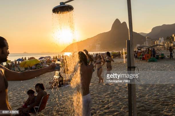 Man fills a plastic bottle with sweet water from beach shower on Ipanema beach.