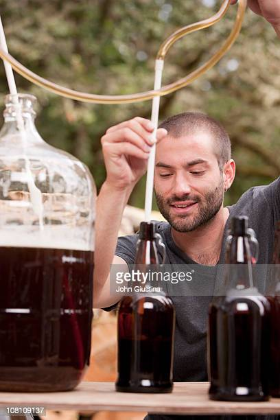Man fills bottles with home brewed beer.