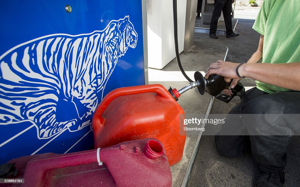 A man fills containers with fuel at an Esso gas station in Vancouver, British Columbia, Canada, on Friday, May 6, 2016. The worst wildfire in Alberta history is boosting Canadian crude prices as oil companies evacuate workers and shut in output. Photographer: Ben Nelms/Bloomberg via Getty Images