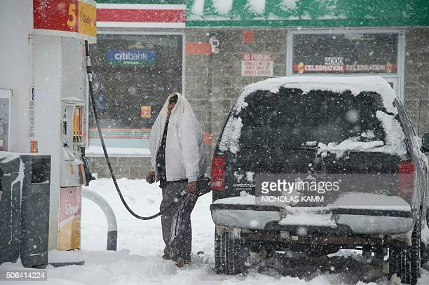 A man fills his car at a gas station during a snowstorm in Washington on January 23 2016 A deadly blizzard with bonechilling winds and potentially...