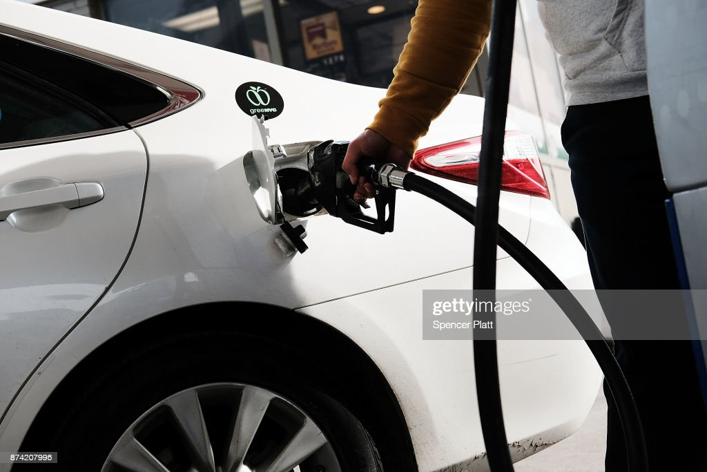 A man fills his car up with gas at a station on November 14, 2017 in New York City. According to a new report by the International Energy Agency, (IEA) global oil demand will fall only slightly alongside the predicted rise in electric vehicles over the next two decades. In its World Energy Outlook 2018, the Paris-based group expects oil prices should continue to rise towards $83 a barrel by the mid-2020s and that the U.S. will be a dominant force in global oil and gas markets for many years to come. The IEA report also predicts that the world will use just over 100 million barrels of oil a day by 2025.