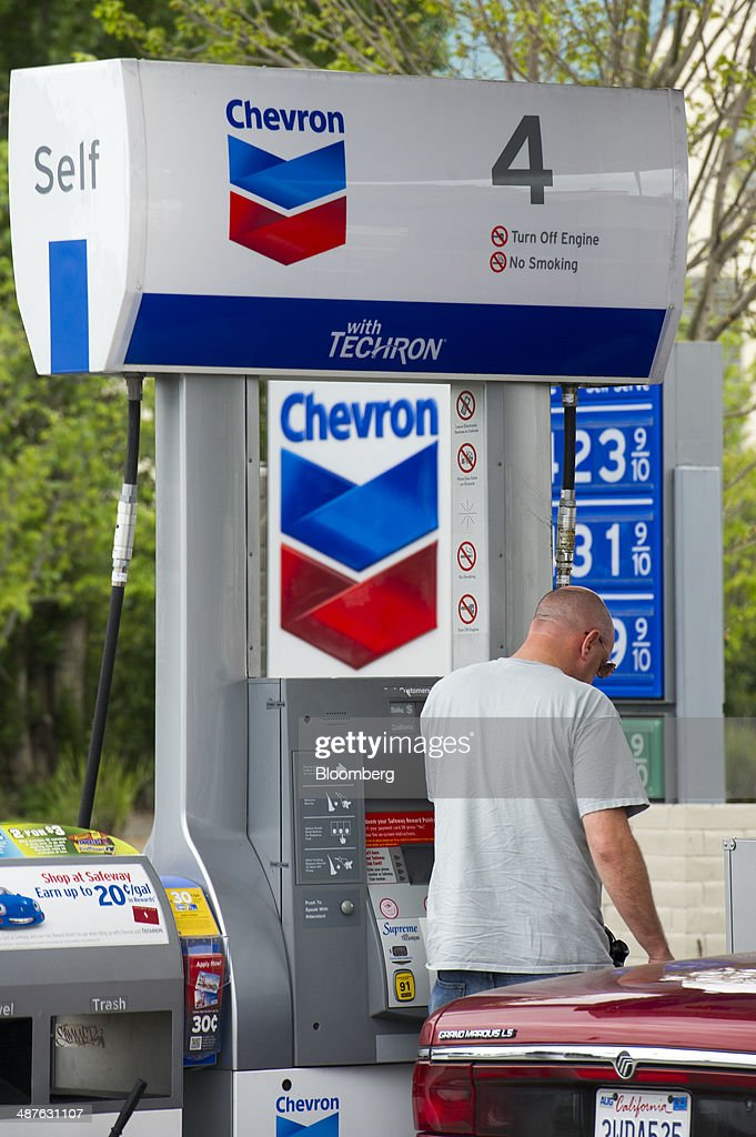A man fills his car with gasoline at a Chevron Corp fueling station in Richmond California US on Thursday April 24 2014 Chevron Corp is expected to...
