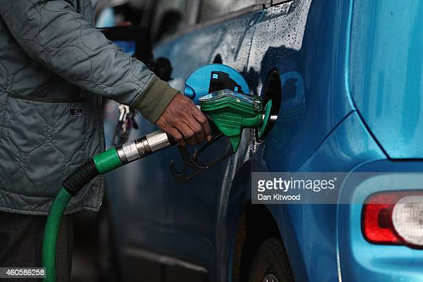 A man fills his car with petrol on December 17 2014 in London England The motoring organisation the RAC has predicted that fuel prices at the pumps...