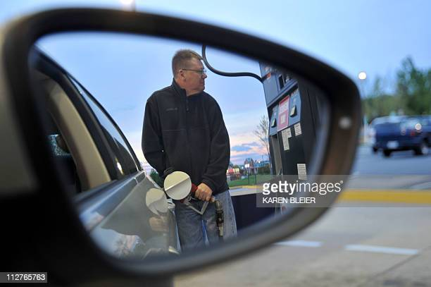 A man fills the gas tank of his car April 21 2011 at a station in Manassas Virginia Gas prices in the US are soaring and in several place including...