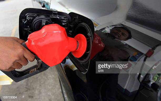A man fills the tank of a car at a petrol station in Kuala Lumpur on June 4 2008 Malaysia's petrol prices will rise 40 percent to 270 ringgit a litre...