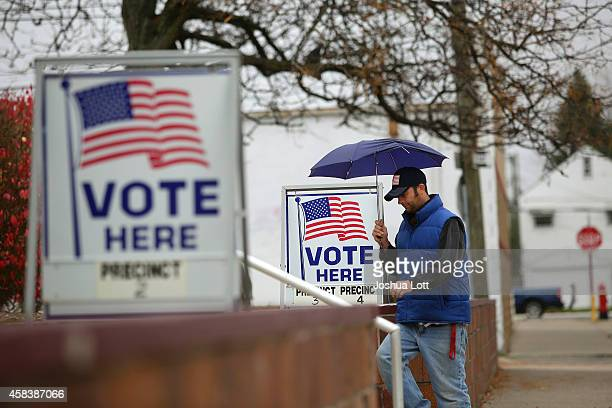 A man fills walks past voting signs displayed outside a polling station during the midterm elections November 4 2014 in Hamtramck Michigan Today...