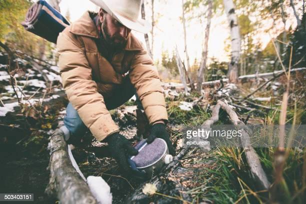 Homme caractérise gourde en randonnée à travers les bois en hiver