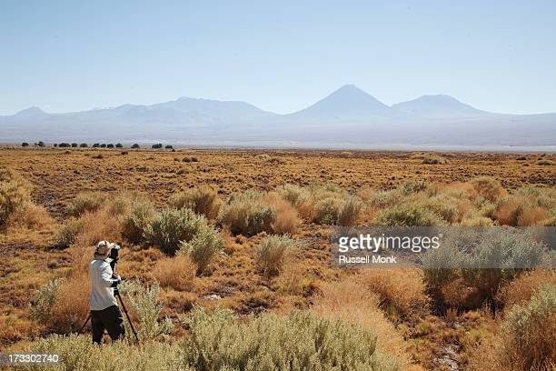 Man filming in a desert landscape