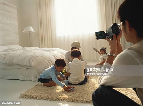 Man filming wife and children (3-7) in bedroom