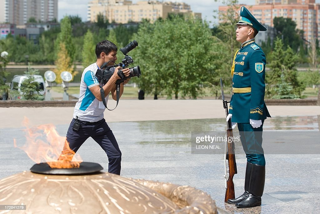 A man films a soldier as he stands guard ahead of a wreath-laying ceremony by British Prime Minister David Cameron at the Monument of the Motherland Defenders in Astana, Kazakhstan on July 1, 2013. David Cameron arrived in Kazakhstan on June 30, 2013 on the first ever trip by a serving British prime minister, hoping to boost trade ties but also promising to raise human rights concerns.