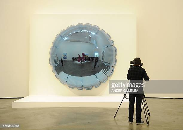 A man films a US artist Jeff Koons' artwork titled 'Moon' during the presentation of the 'Jeff Koons Retrospective' exhibition at the Guggenheim...