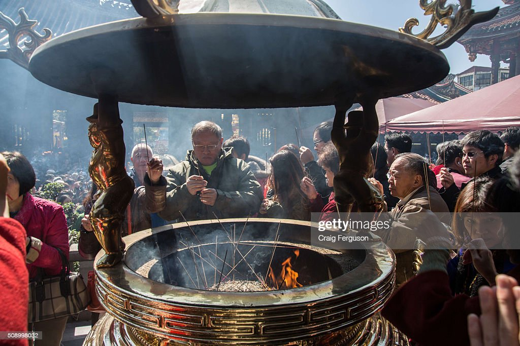 A man finds a space in the crowd to offer incense to the gods and pray for good fortune. On the first day of the Chinese lunar year it is traditional to visit temples to light incense and pray for a prosperous year. Thousands come to Longshan Temple, one of the oldest and most important in Taipei every year.
