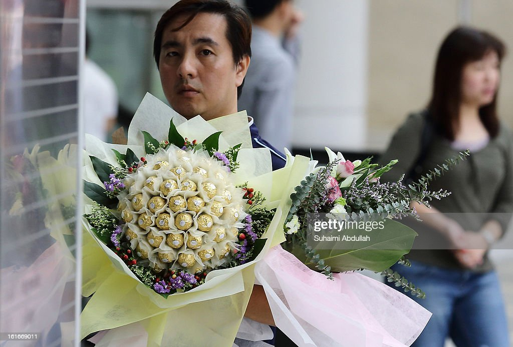 A man finds his way to deliver a Ferrero Rocher chocolate flower bouquet during Valentine's Day at Raffles Place on 14 February, 2013 in Singapore. Valentine's Day is a time to celebrate love, romance and friendship and is celebrated worldwide annually in different ways on February 14.
