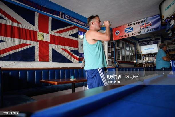A man finishes his pint as he stands in front of a large Union flag in the 'Bar None' pub on July 26 2017 in Benalmadena Spain With Brexit...
