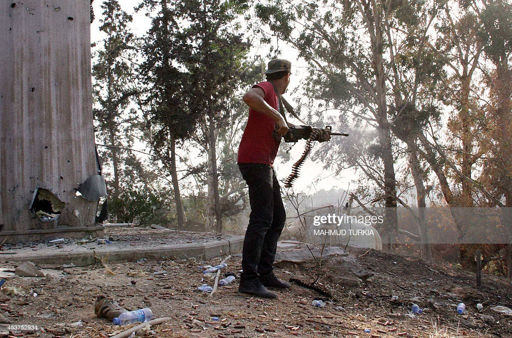 A man fires a weapon during fightings between rival militias around Tripoli international airport on August 17 2014 The skirmishes have centred...