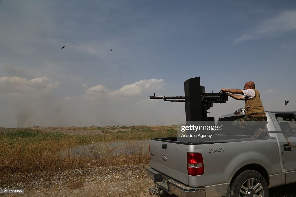 A man fires heavy machine gun during clashes between Daesh and Peshmergas on Guve side of Peshmerga in Mosul's Mahmur district, Iraq on May 3, 2016.