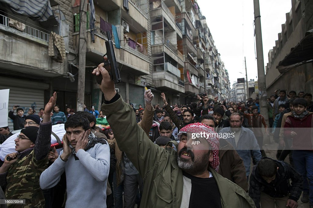 A man fires his gun in the air during a funeral procession in the Bustan al-Qasr district of Aleppo, on January 30, 2013. Syria's opposition charged that 'global inaction' was giving Bashar al-Assad's regime a license to kill, a day after dozens of young men were found shot execution-style in the city of Aleppo. AFP PHOTO/JM LOPEZ