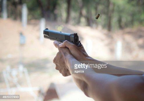 Man firing pistol at firing range : Stock Photo