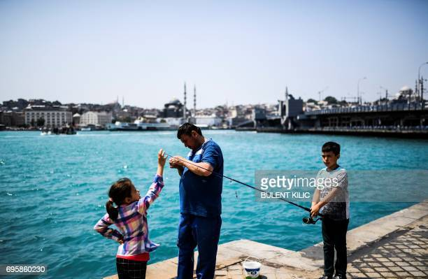 A man fish with his children at Karakoy after Bosphorus has turned turquoise due to phytoplankton on June 14 in Istanbul The Moderate Resolution...