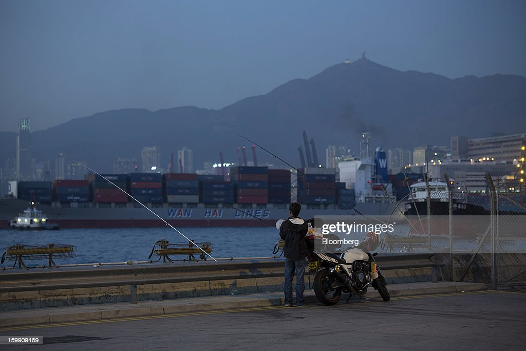 A man fishes as a Wan Hai Lines Ltd. container ship sails past the Kwai Tsing Container Terminals in Hong Kong, China, on Monday, Jan. 21, 2013. Hong Kong is scheduled to release export figures for December on Jan. 24. Photographer: Jerome Favre/Bloomberg via Getty Images