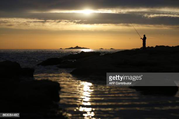 A man fishes at sunset off Ajaccio on the French Mediterranean Island of Corsica on October 19 as the Sanguinaires Islands are seen in the background...