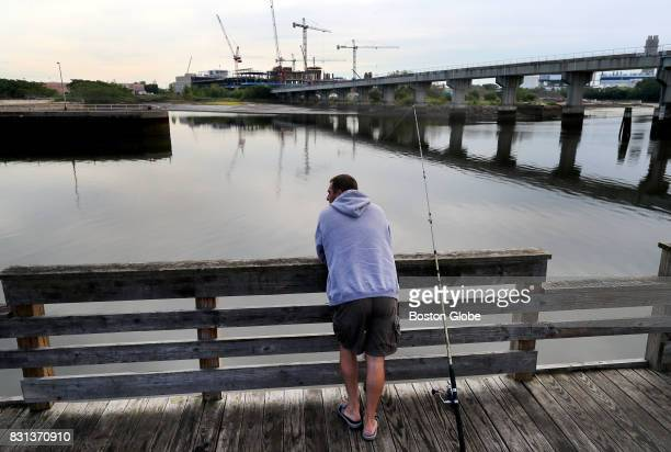 A man fishes from a pier on the Mystic River behind Assembly Row in Somerville MA near where construction on the new Wynn Casino takes place across...
