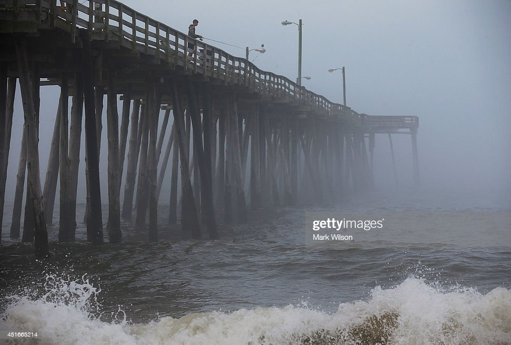 A man fishes from the Nags Head Pier as fog and heavy surf roll in on July 3 2014 in Nags Head North Carolina Hurricane warning has been issued for...