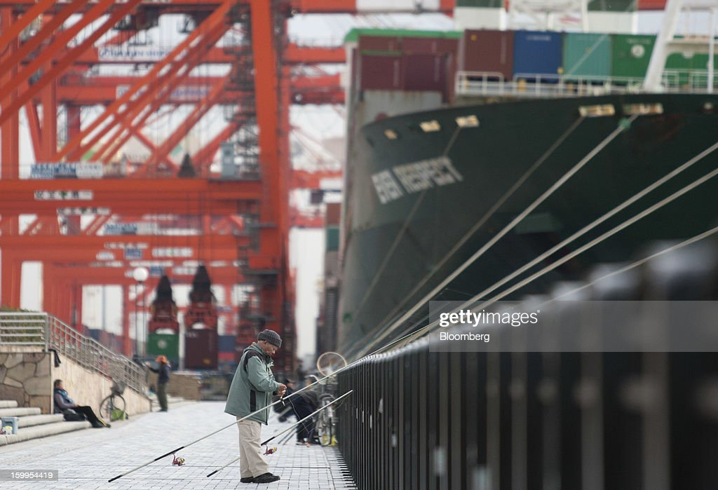 A man fishes in front of a container ship moored at a shipping terminal in Tokyo, Japan, on Wednesday, Jan. 23, 2013. Japan's exports fell more than analysts forecast and the annual trade deficit swelled to a record, bolstering the case for Prime Minister Shinzo Abe to weaken the yen even as trade tensions mount. Photographer: Tomohiro Ohsumi/Bloomberg via Getty Images