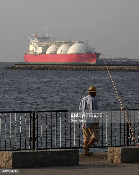 A man fishes in front of a liquefied natural gas tanker berthed at Tokyo Electric Power Co's Futtsu gasfired thermal power plant in Futtsu Chiba...